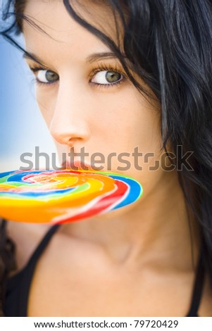 Beautiful Bikini Female With Stunning Hazel Eyes With Surprised Expression Sucking On A Rainbow Candy Lollipop With A Blue Sky Background - stock photo