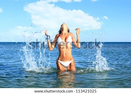 Beautiful bikini model splashing water - stock photo