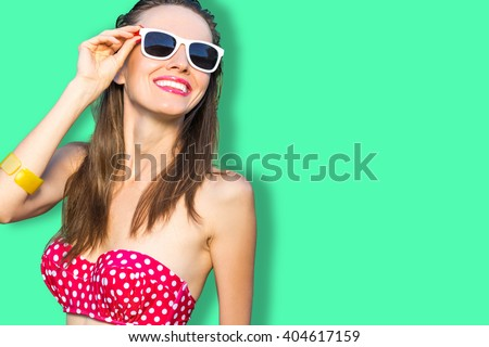 Beautiful bikini summer woman wearing red swimsuit and sunglasses over green background - stock photo