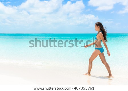 Beautiful bikini woman walking relaxing on sunny perfect white sand beach and pristine turquoise clear water in idyllic tropical destination during summer travel. Luxury getaway vacation. - stock photo