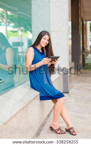 Beautiful biracial Asian Caucasian teen girl holding tablet computer sitting outside store window - stock photo