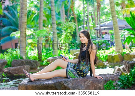 Beautiful biracial Asian Caucasian teen girl sitting on rock in tropical setting looking at cellphone, palm trees in background - stock photo