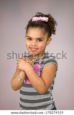 Beautiful biracial six year old little girl standing with arms folded.  - stock photo