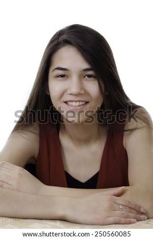 Beautiful biracial teen girl in red dress sitting arms crossed, smiling - stock photo