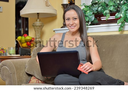 Beautiful biracial woman (Asian and Caucasian) laying on couch and using her laptop computer - holding credit card - online shopping - stock photo