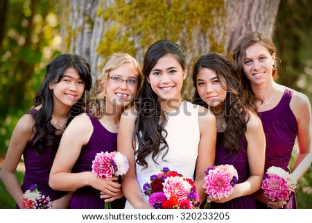 Beautiful biracial young bride smiling with her multiethnic group of four bridesmaids in purple dresses - stock photo