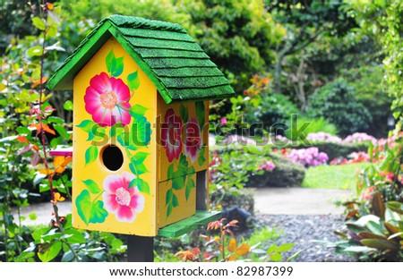 Beautiful bird house in a lush garden - stock photo