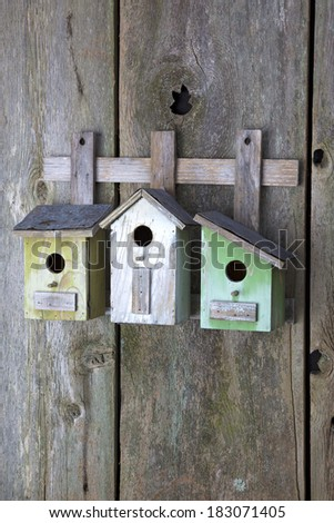 Beautiful birdhouses on old wooden fence - stock photo