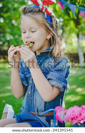 Beautiful birthday 7 years old girl outdoors with pizza instead of birthday cake - stock photo