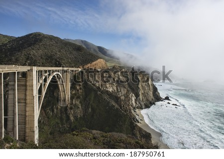 Beautiful Bixby Bridge, Big Sur, California, fog hanging along the edge of Hwy 1 - stock photo