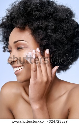 Beautiful black african model with flawless skin smooth complexion applying moisturiser face cream to her cheek, beauty cosmetics skincare concept - stock photo