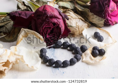 beautiful black beads on white wooden table with dried red and white roses - stock photo