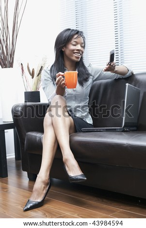 beautiful black businesswomen on the phone at home laughing - stock photo