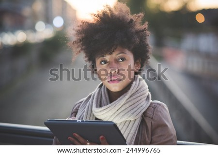 beautiful black curly hair african woman using tablet in town by night