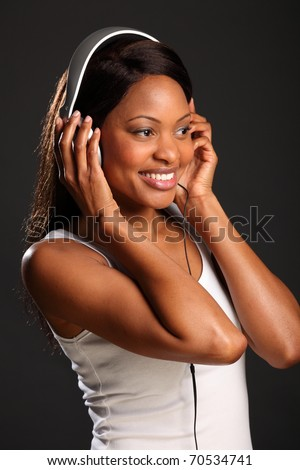 Beautiful black girl smiling listening to music - stock photo