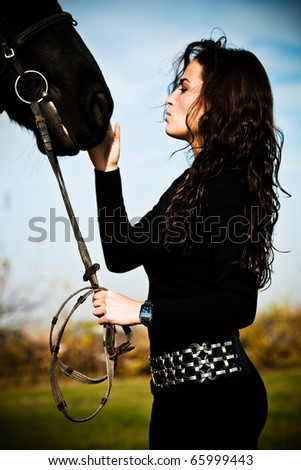 beautiful black hair woman and black horse outdoor day shot
