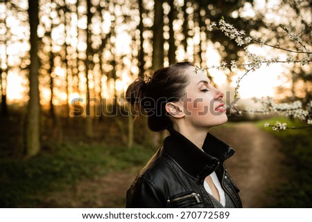 Beautiful black hair woman enjoying blooming tree from profile, pretty girl relaxing outdoor.  Happy young lady and spring green nature. Low depth of field. - stock photo