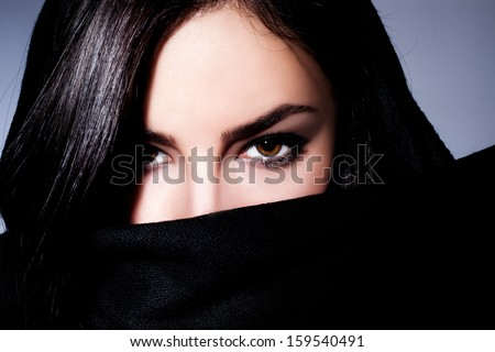 beautiful black hair woman with black scarf over her face, studio closeup - stock photo