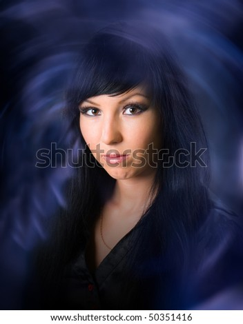 Beautiful black-haired witch - stock photo