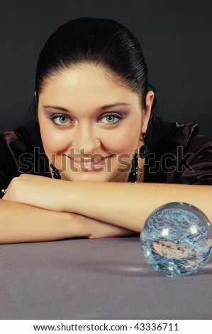 Beautiful black-haired witch holding the magic sphere in both hands - stock photo