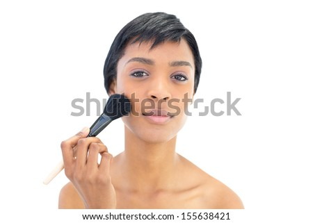 Beautiful black haired woman applying powder on her cheeks on white background - stock photo