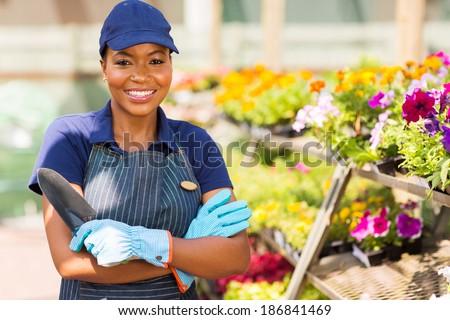beautiful black nursery worker in greenhouse - stock photo
