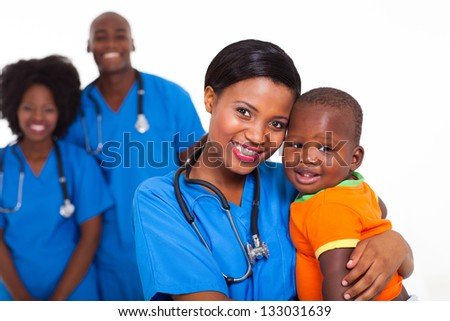 beautiful black pediatrician and baby boy with co-workers on background - stock photo
