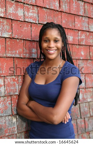 beautiful black teen next to red weathered shingle siding