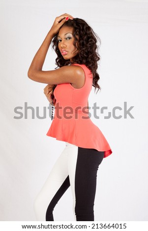 Beautiful black woman in pink blouse, standing with her hands in her hair, looking thoughtfully at the camera - stock photo