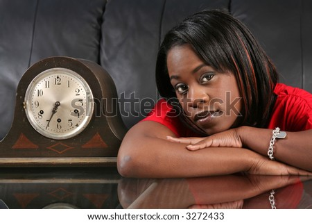 beautiful black woman leaning on a table by an old clock waiting and thinking - stock photo