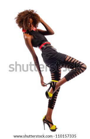 Beautiful black woman leans back as she raises her foot and grabs her heel while isolated on a white background. - stock photo