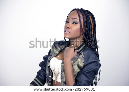 Beautiful black woman posing in a studio wearing a white tube top, camo jacket, heels and jeans. - stock photo
