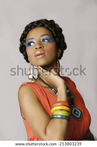 Beautiful black woman posing in orange dress, wearing colorful jewelry and makeup, with her hair in a braided style, looking back over her shoulder. - stock photo