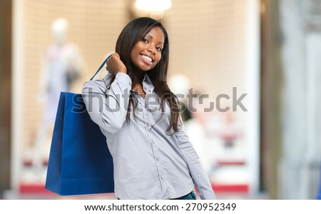 Beautiful black woman smiling and holding shopping bags - stock photo