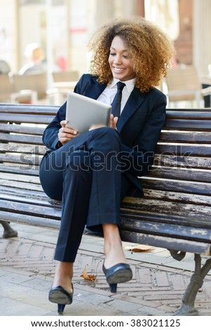 Beautiful black woman smiling and using tablet computer in urban background Businesswoman wearing suit with trousers and tie.