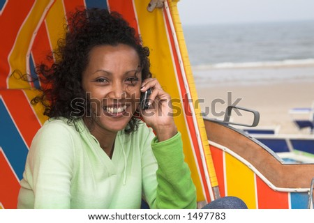 Beautiful black woman talking on the phone sitting in a beachchair on a windy day at the beach
