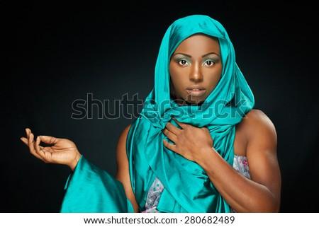 beautiful black woman with aquamarine scarf on black background   - stock photo