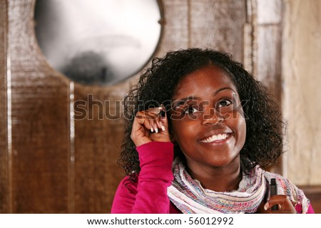 beautiful black woman with big eyes applying mascara