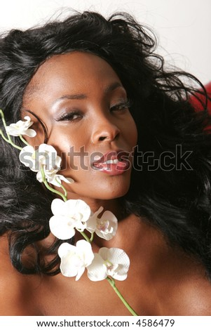 Beautiful black woman with white orchid - stock photo