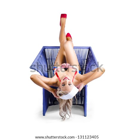 Beautiful blond american pin-up woman in red and white top upside down in purple colored wickerwork chair isolated on white background - stock photo
