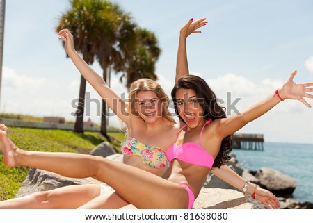 Beautiful blond and brunette young women enjoying South Pointe Park in Miami Beach. - stock photo