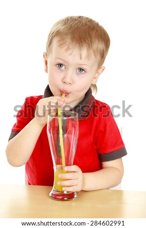 Beautiful blond boy drank through a straw big glass of juice, sitting at the table- isolated on white background - stock photo