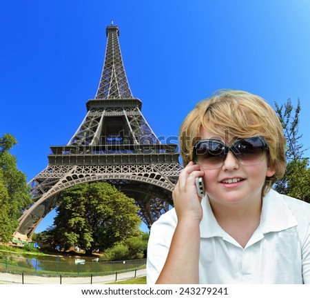 Beautiful blond boy having fun chatting with friends on a cell phone. Background - the Eiffel Tower. The picture was taken Fisheye lens - stock photo