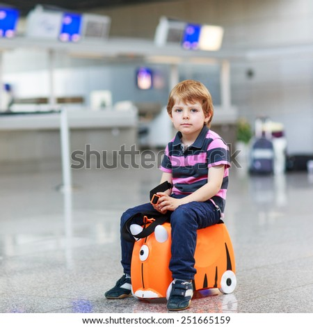 Beautiful blond boy having fun with suitcase at airport, indoors. Going on holidays. Empty counters as of a strike in Germany.