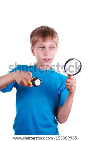 Beautiful blond boy in a in a blue t-shirt holds a flashlight and a magnifying glass looking for something  - stock photo
