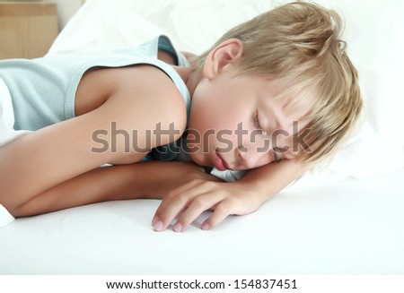 Beautiful blond boy sleeping peacefully in a bed (isolated on white background) - stock photo