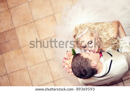 beautiful blond bride and groom kissing. top view - stock photo