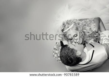 beautiful blond bride and groom kissing. top view. text place - stock photo