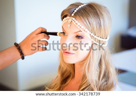 Beautiful blond bride doing makeup in her wedding day near mirror. Bride makeup. - stock photo