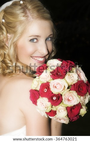 Beautiful blond bride holding a rose bouquet